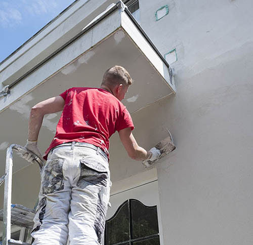 worker on a ladder completing stucco installation on a florida home