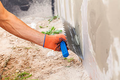 worker holding special hand tool used to apply stucco to a wall
