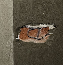 wall needing stucco repair with exposed wire